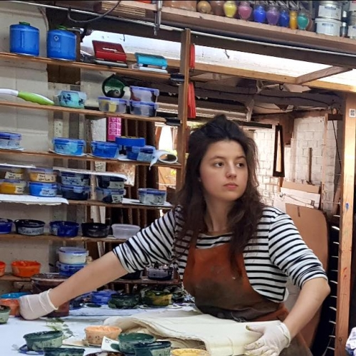 A girl in a studio surrounded by paint pots