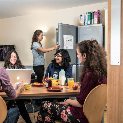 A group of Falmouth University students sat round a table having breakfast in university halls