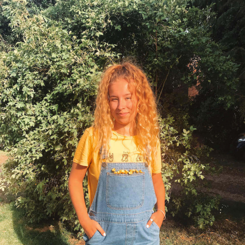 A Falmouth University student wearing denim dungarees and standing near bushes