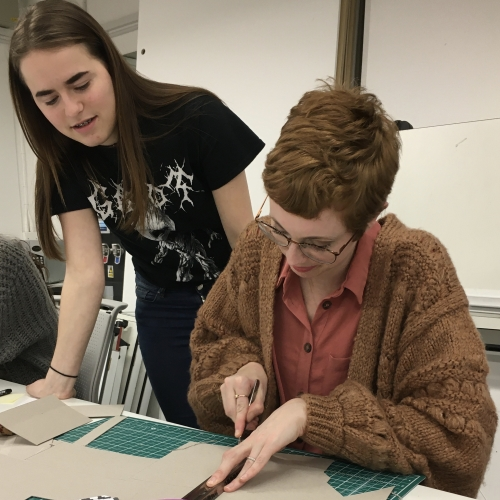 Student Hollie Milne making a model with fellow student looking on