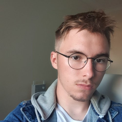 A male student wearing glasses and a denim jacket