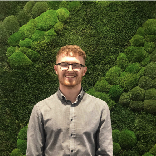 Will Dorrell Business and Entrepreneurship graduate standing in front of green moss wall.