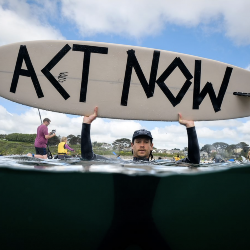 Activist in the sea holding up a surfboard with Act Now message written on it