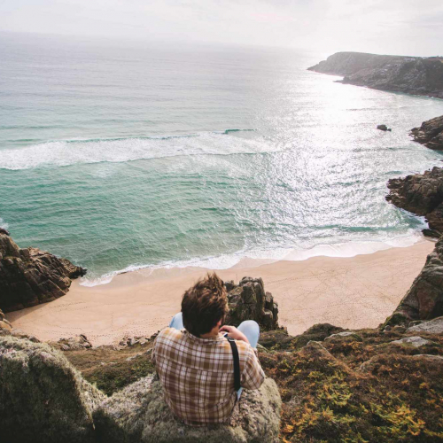 A Falmouth University student sitting on a cliff top overlooking a beach and sea
