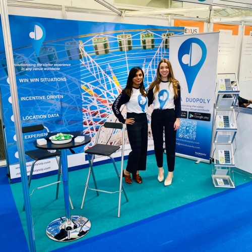 Two women standing together in a blue Data Duopoly exhibition stand
