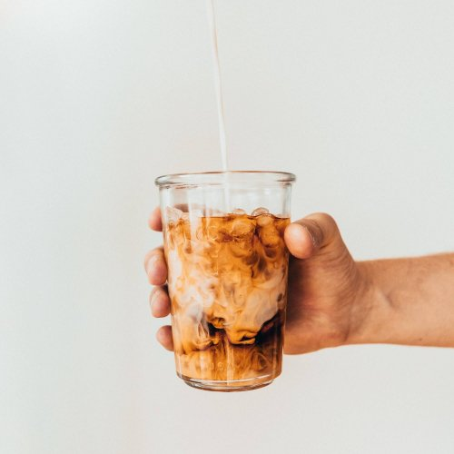 Photo of hand holding out a glass of iced coffee. Photo by Tavis Beck.