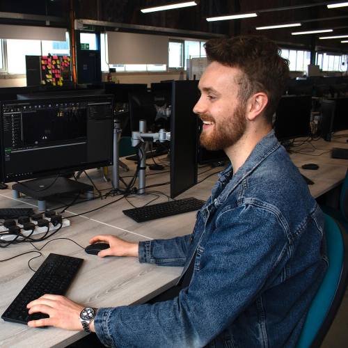A Falmouth University Games student smiling at a computer screen with a keyboard and mouse