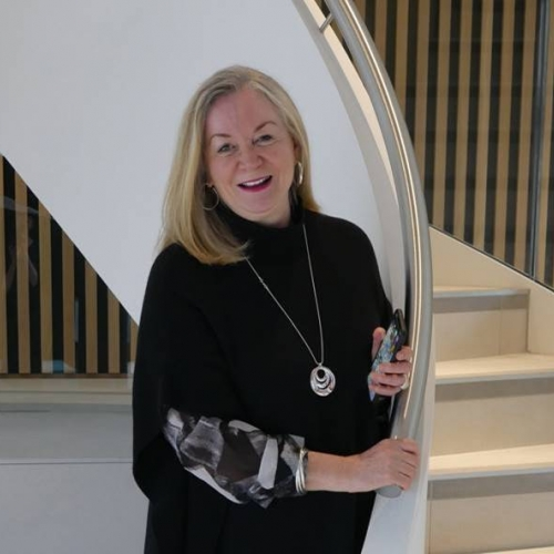Professor Anne Carlisle in front of a staircase
