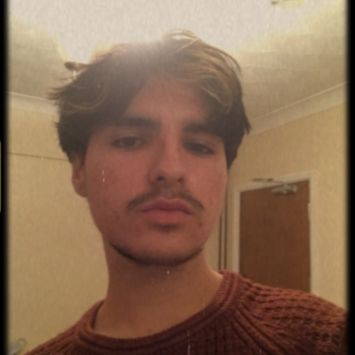 A Falmouth University student with a moustache, wearing a dark orange jumper