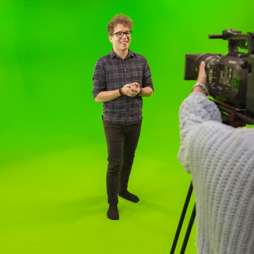 Student being filmed with bright green screen studio.