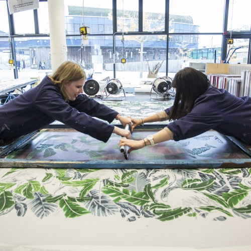 Two students pulling squeegee over large screen for screen printing.