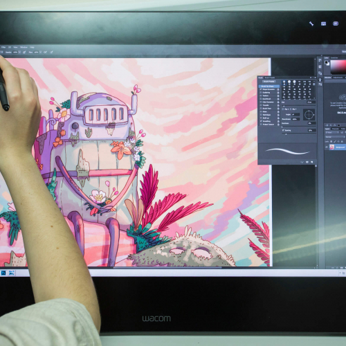Animation student drawing a robot on a graphic tablet