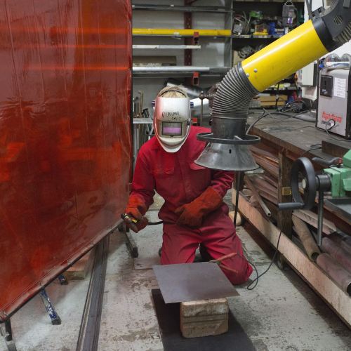 Falmouth student working in workshop with head mask on.