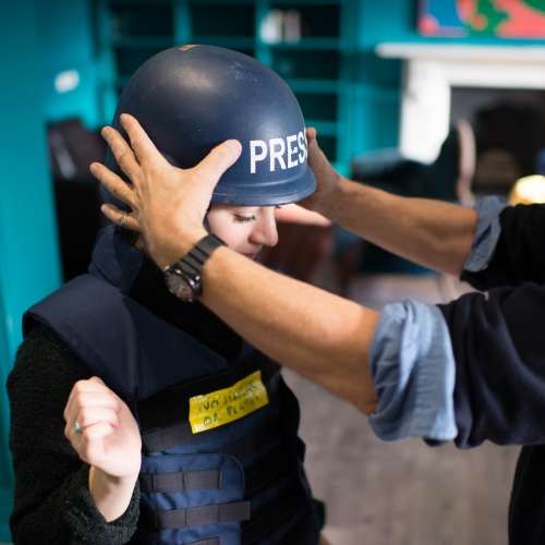 Journalism student trying on a press helmet.