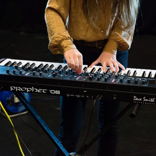 Female students hands playing keyboards and adjusting controls