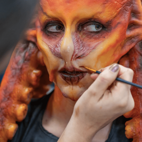 A person wearing a prosthetics orange mask with a hand and a paintbrush