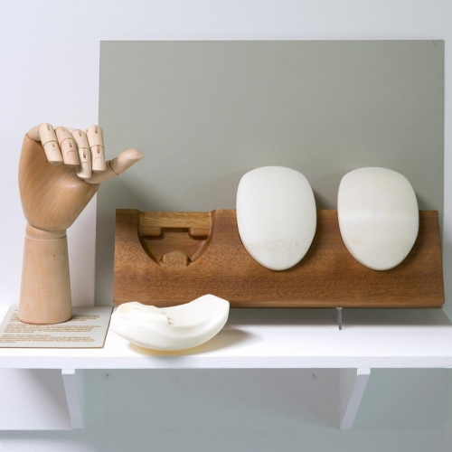 Wooden hand on display next to white oval shapes.