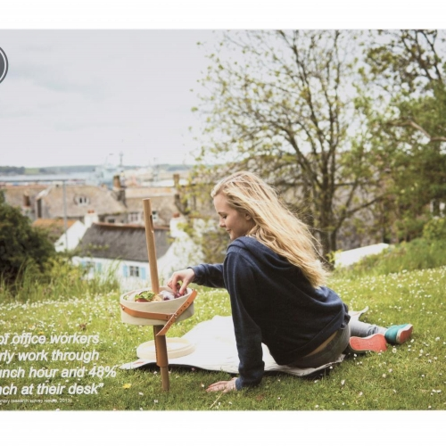 Girl sitting on grass and eating out of a tray table held by a stick in the ground.