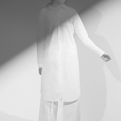 Model in white long shirt dress and loose trousers, angular shadow falling across her.