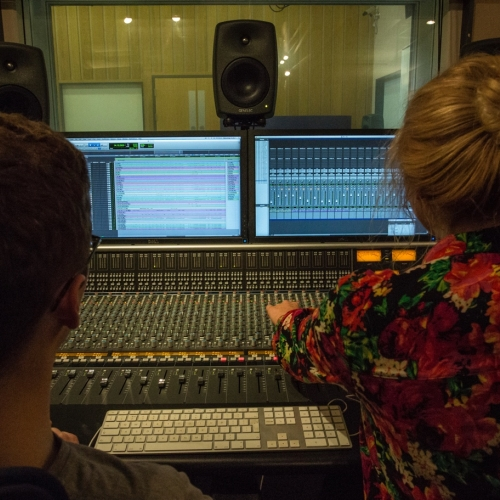 View from behind two students adjusting controls on mixing desk in studio