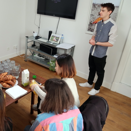 Students visiting design studio, pouring coffee and plate of croissants