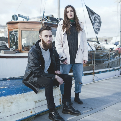 Couple posing by boat in fashionable rainwear, knitwear and black boots.