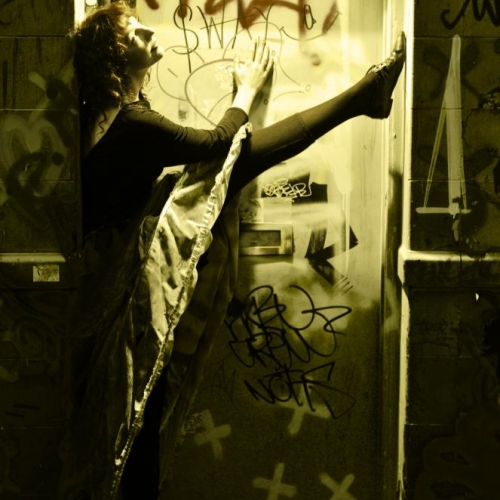 Actor in graffitied booth holding arm and leg up high.