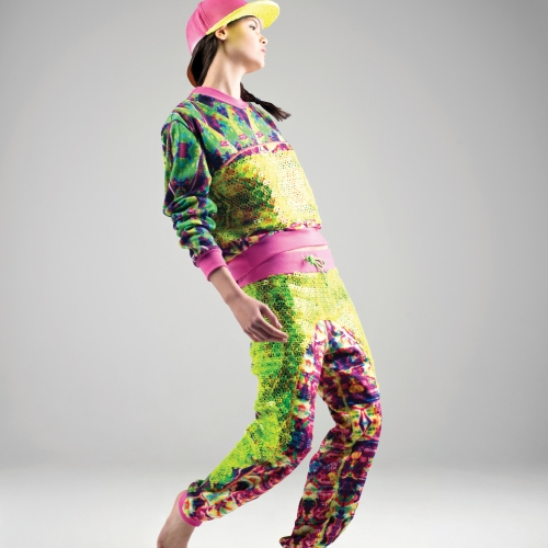 Model in bright coloured and patterned tracksuit with pink and yellow baseball cap.