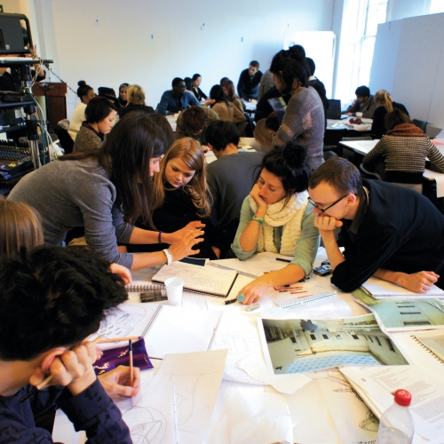 Room full of students busy working around tables on an interiors project.