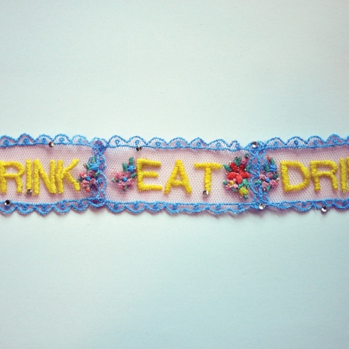 Lace trimming embroidered with flowers and the words eat and drink.