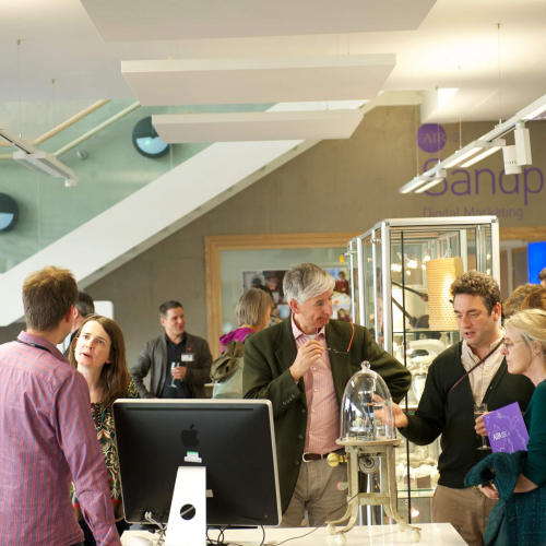 People standing round and chatting at an exhibition at Falmouth University