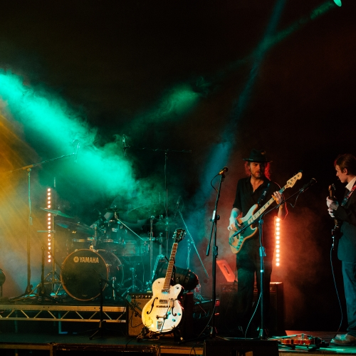 Two guitarists on stage lit with yellow, green and red lights.