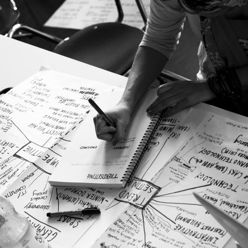 Grayscale image of students hands writing and filling pages in front of them with ideas