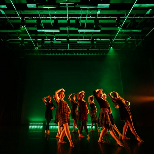 Group of dancers with arms to head and pointing a leg out on a green lit stage.