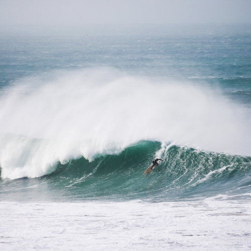 A surfer riding a large breaking wave