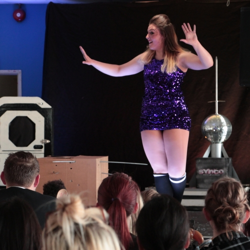 A performer in purple sequins on stage at Abracadabra event