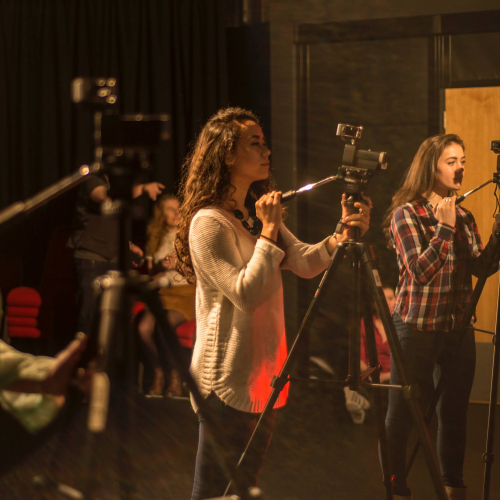 Three students filming with cameras in a studio at Falmouth University