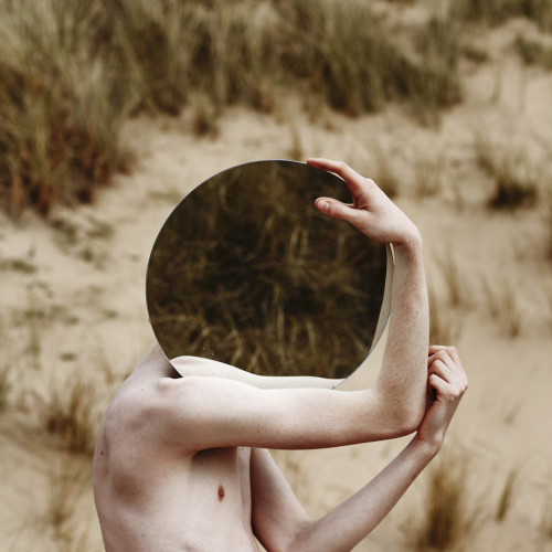 Bare chested model carrying circle mirror in front of face reflecting grass.