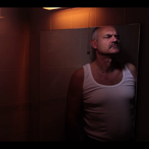 A bald man in a mirror wearing a white vest in low light