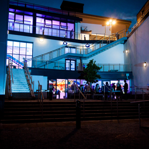 AMATA building with external staircases lit up in blue and purple.