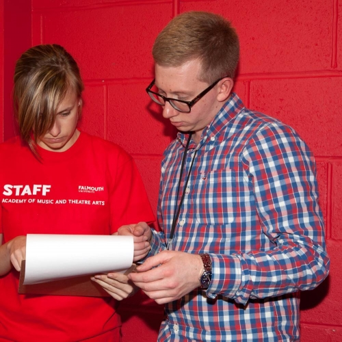 Amata staff and a student stood in front of a red wall looking at a piece of paper.