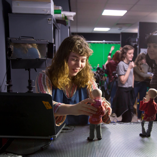 Animation student posing a model figure in a studio