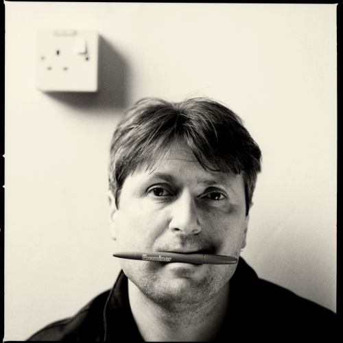 Portrait of Simon Armitage, Visiting Professor of Writing, pen in his mouth.