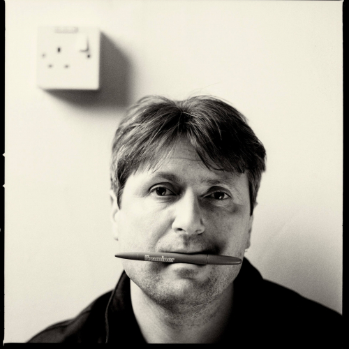 Portrait of Simon Armitage, with a pen in his mouth.
