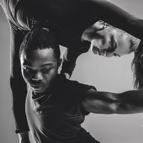 Dancer lifting partner and creating triangle shape with arms