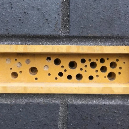 A yellow Bee Brick in a black wall