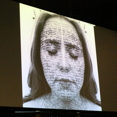 Image on a screen of a girl with writing across her face and neck.