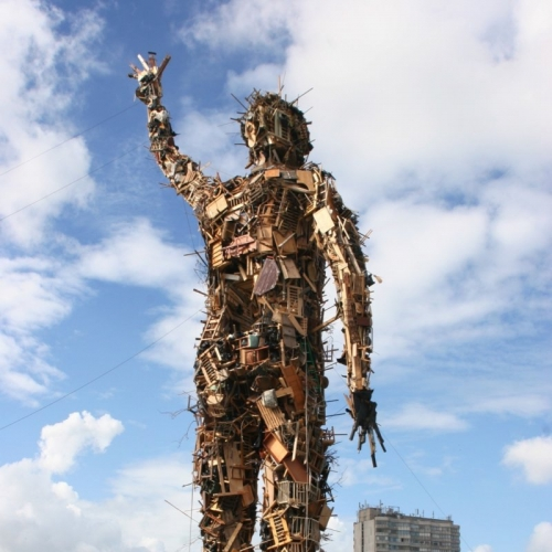Tall statue of figure made of wooden furniture