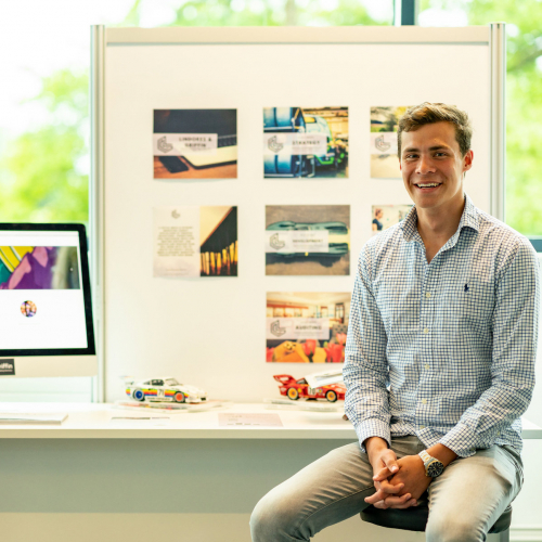Falmouth University Business students in shirts sat in front of desk with work displayed.