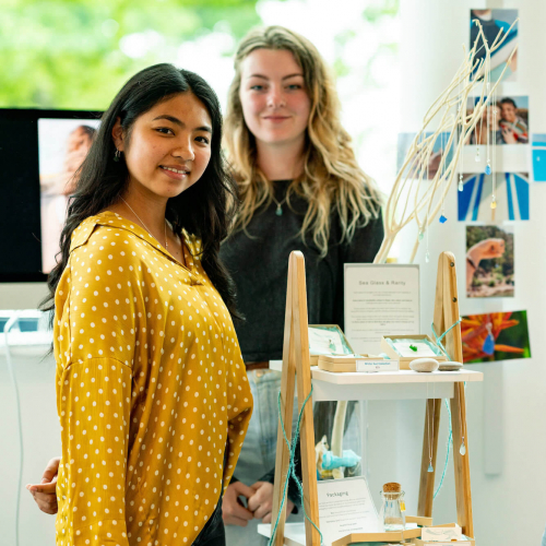 Three Business students stood in front of a stand of their work.